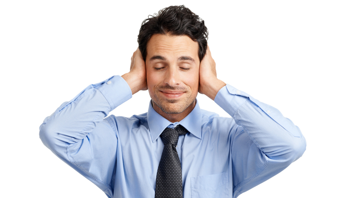 Young businessman looking placid while covering his ears